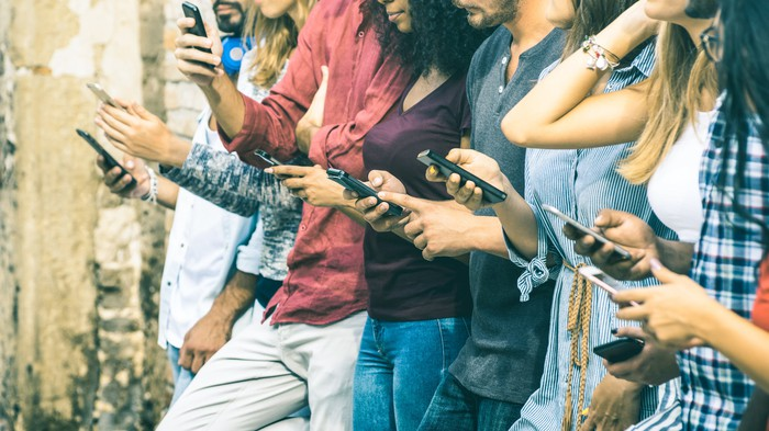 A row of people looking at their phones