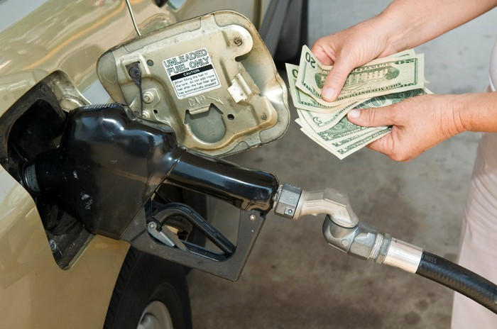 Someone counts money while a gas pump fills a car with gas.