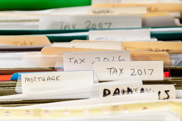 A drawer of file folders labeled for different tax years.