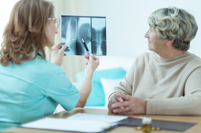 Medical practitioner reviews X-rays with elderly patient.