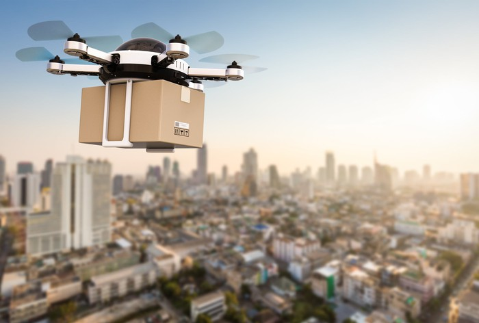 A drone flying a package over a city