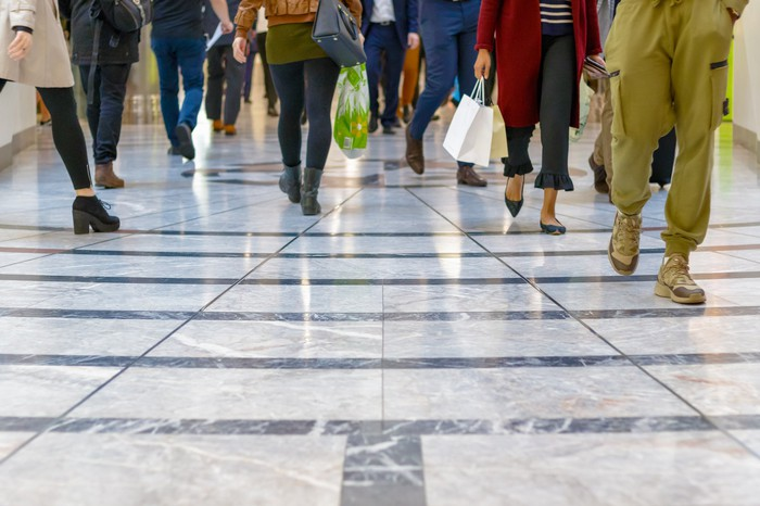 People walking in a mall with a glossy floor