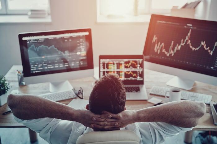 Man at desk watching financial charts on three monitors.