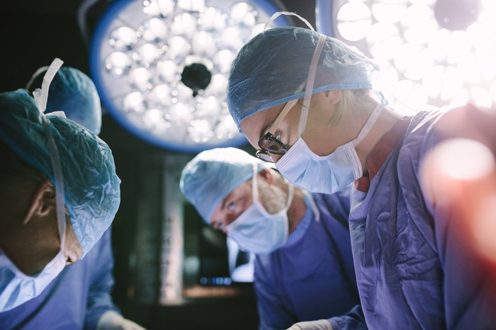 Faces of surgeons bent over an operating table.