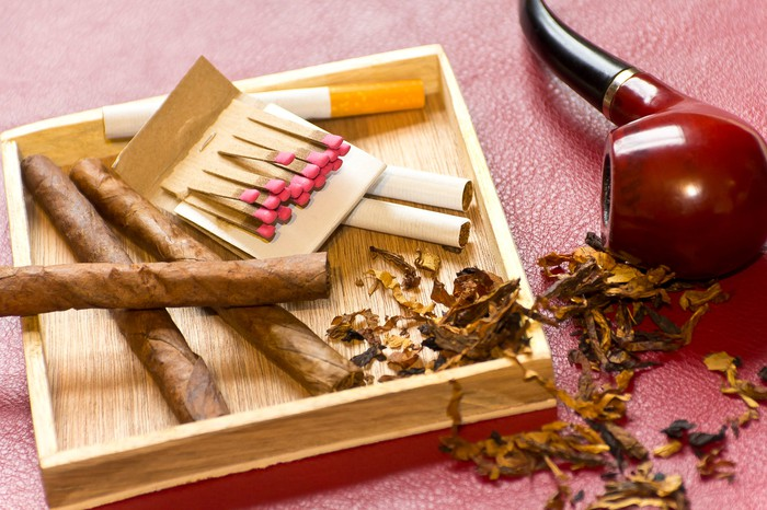 Loose cigarettes and a pack of matches next to a pipe on its side and some loose tobacco