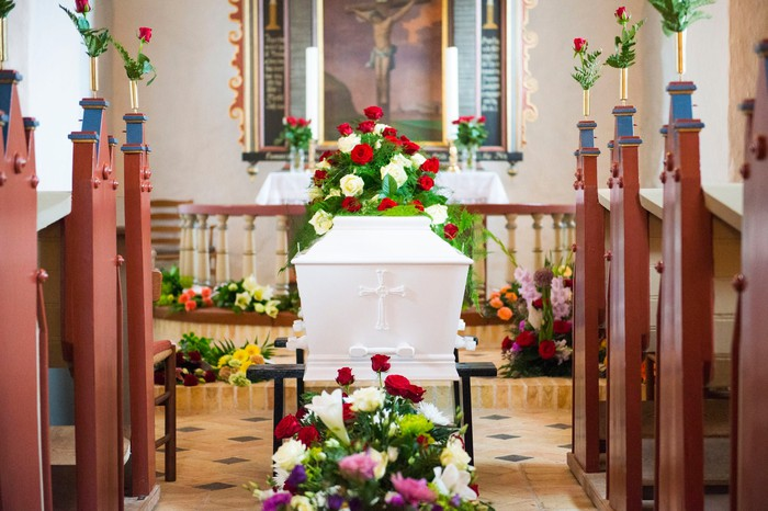 White coffin covered in flowers inside church