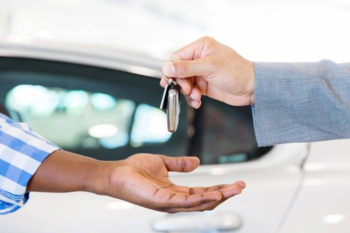 A dealer handing over car keys to a customer