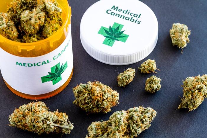 Marijuana buds sit on a table beside an open prescription bottle.
