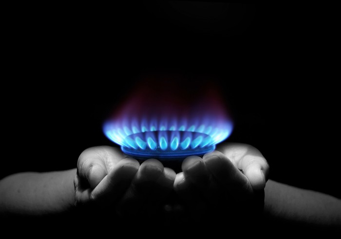 Two cupped hands holding a ring of natural gas flames.