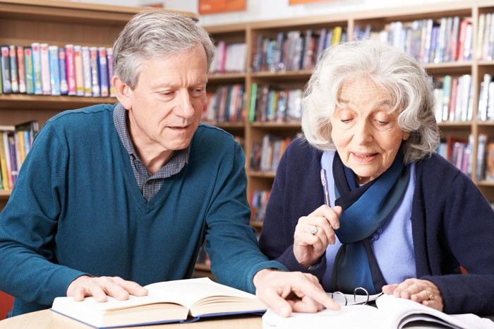 Mature couple reading books in a library.