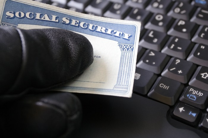 hand in black glove suspiciously holding Social Security card by keyboard