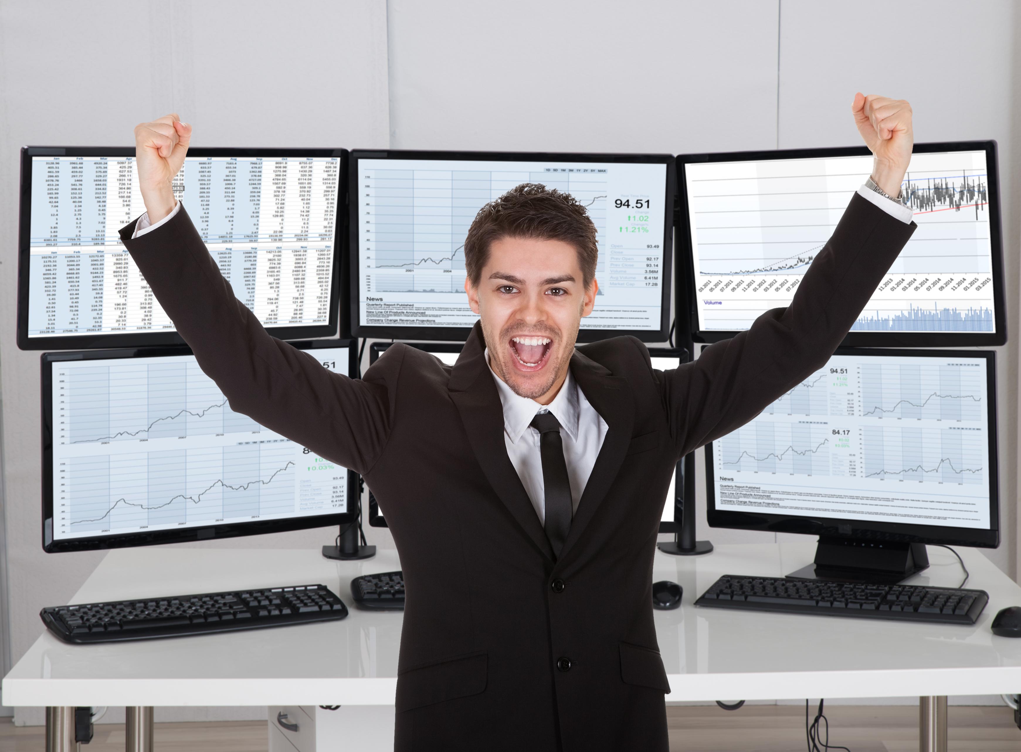 Stock broker celebrating in front of multiple computer screens.