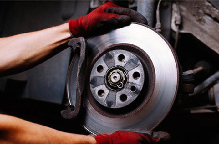 Gloved hands on a car brake and rotor.