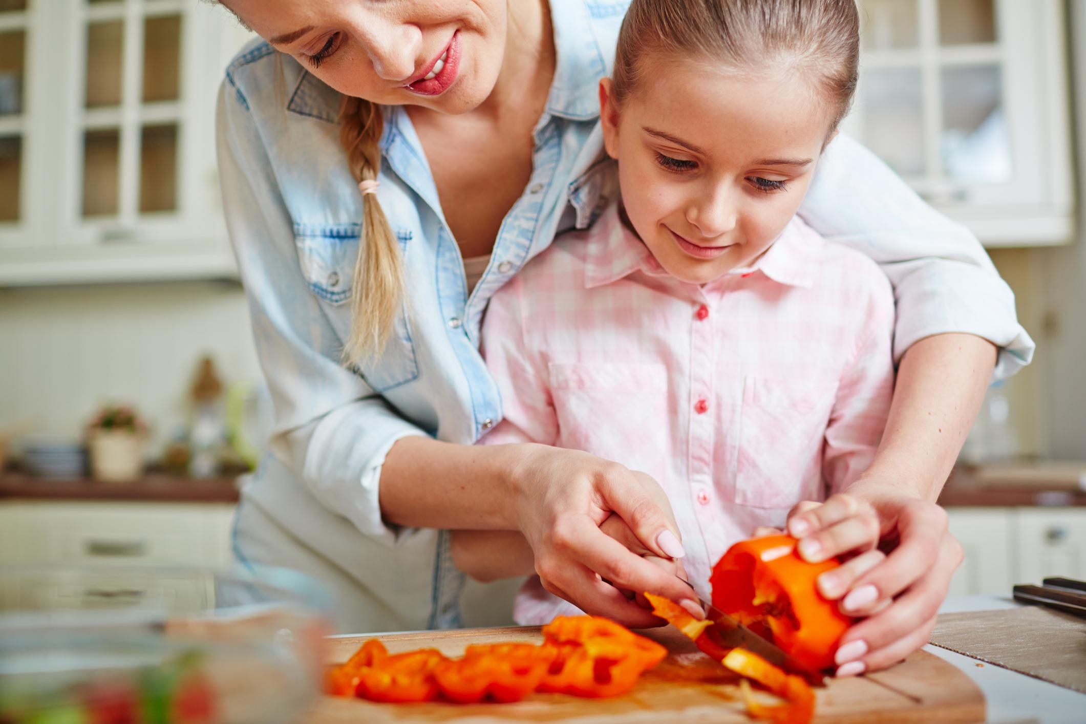 Woman helps child slice an orange pepper.