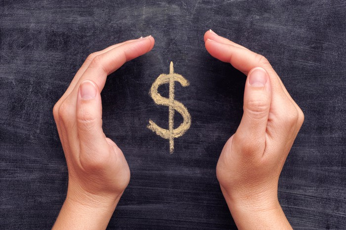 Cupped hands framing a dollar sign written on a blackboard.