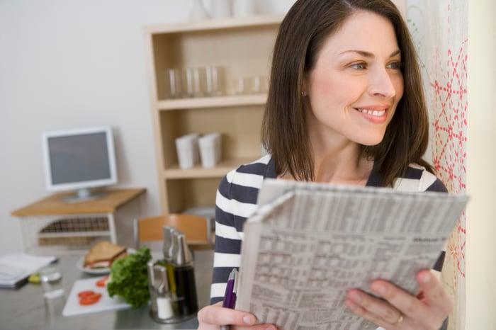 Woman reading financial newspaper.