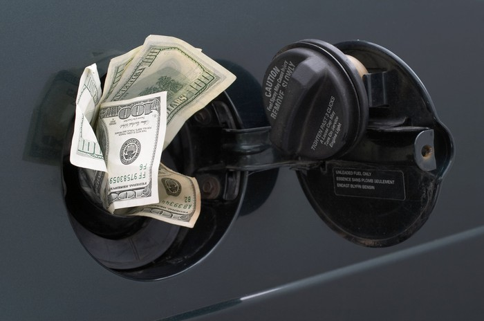 Dollars sticking out of a car gasoline tank.
