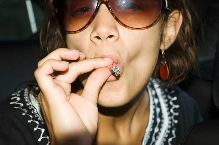 A young woman inhales deeply from a marijuana cigarette.