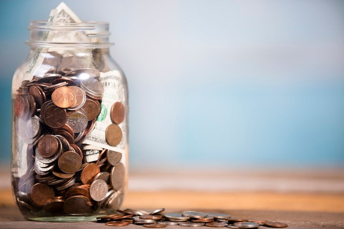 A glass jar stuffed full of coins and currency.