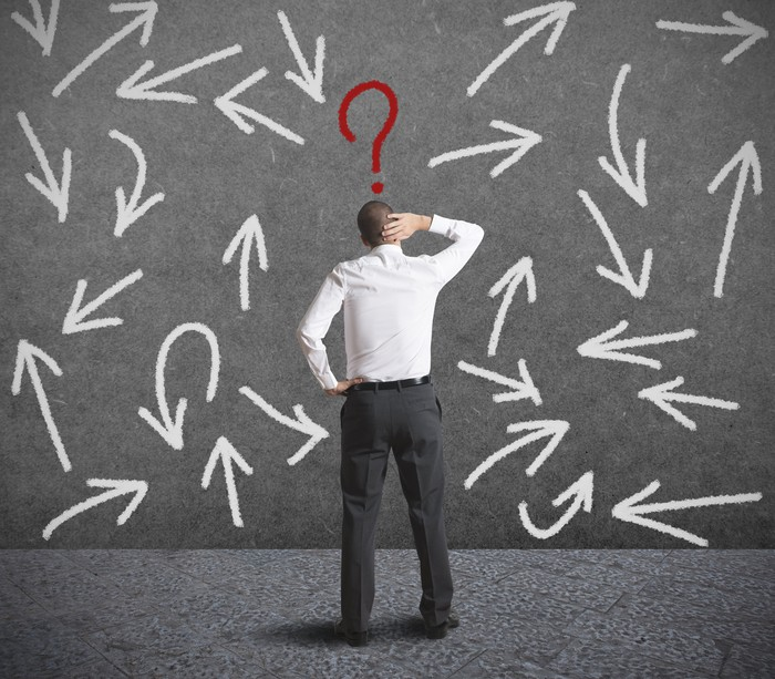 Man standing in front of question marks.
