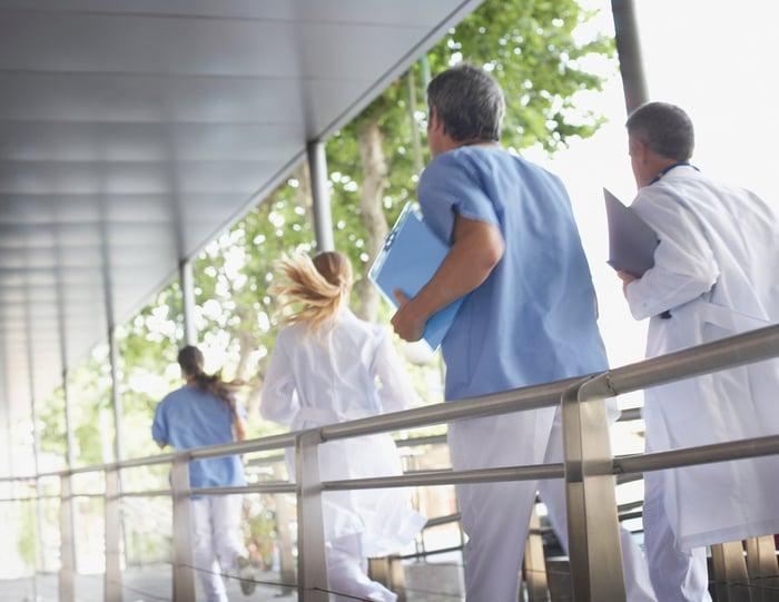 Healthcare providers racing down a corridor.