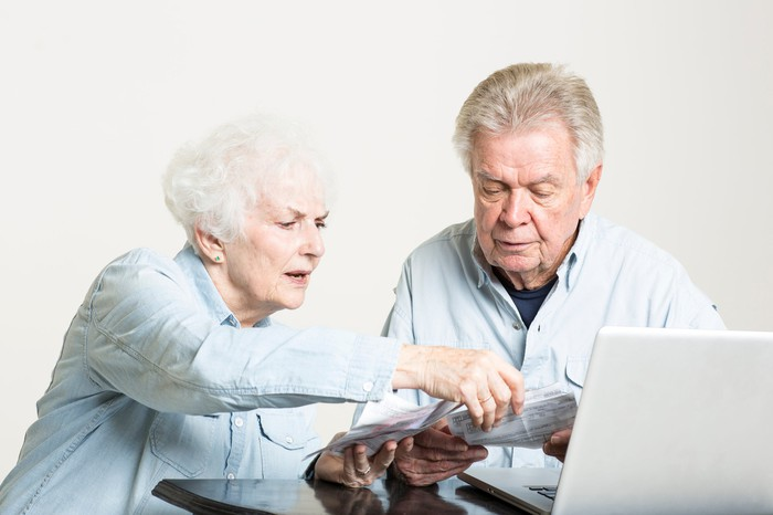Senior couple looking worried while sorting through financial accounts.