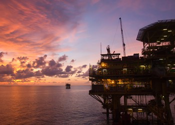 Silhouette of an offshore oil rig at sunset