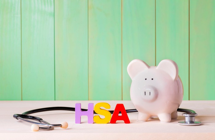 Piggy bank next to stethoscope and acronym HSA
