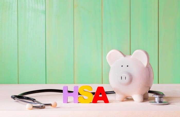 Piggy bank next to stethoscope and acronym HSA