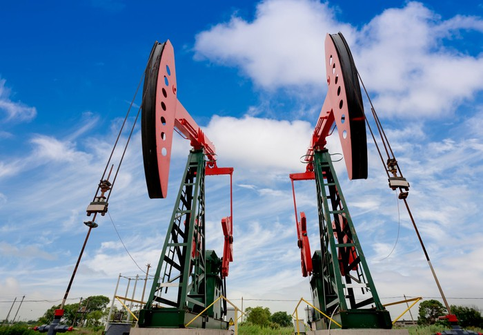 Two oil wells side-by-side with a blue sky in the background.
