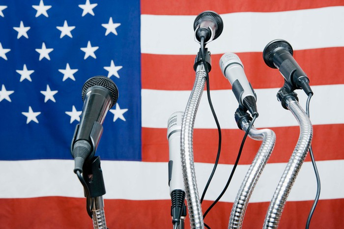 Microphones in front of a US flag