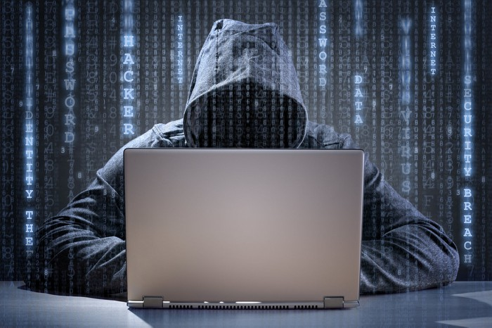 Hooded hacker sitting at a computer.