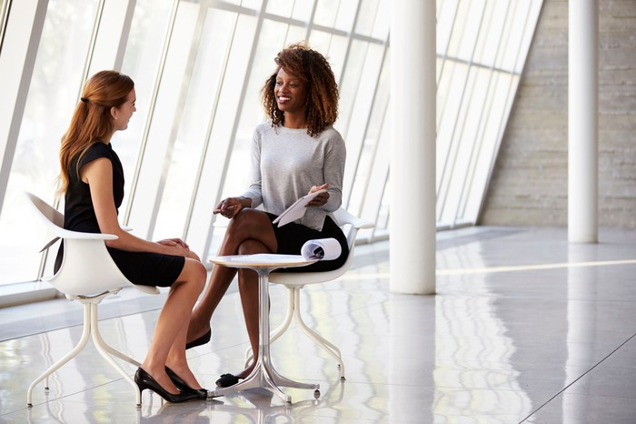 Two professional women speaking in a white, spacious office