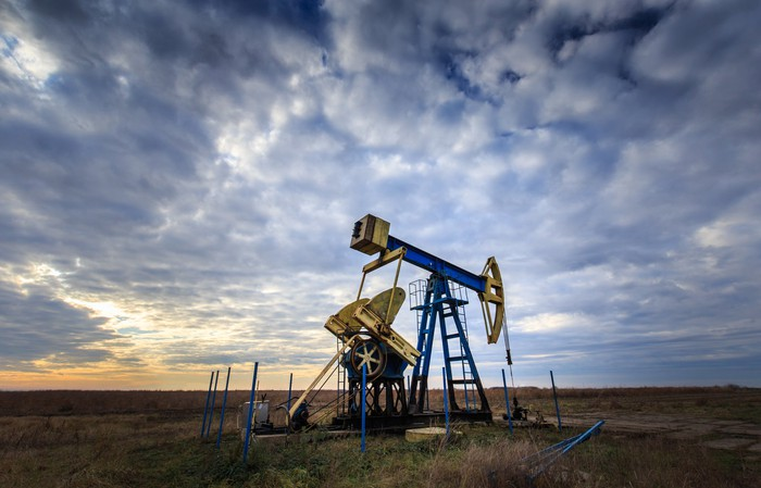 Operating oil and gas well profiled on sunset sky.