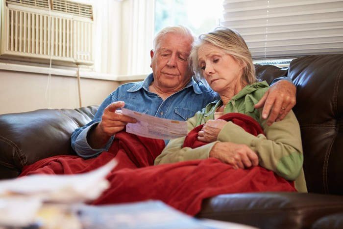 Senior couple examining bills, worried about debt