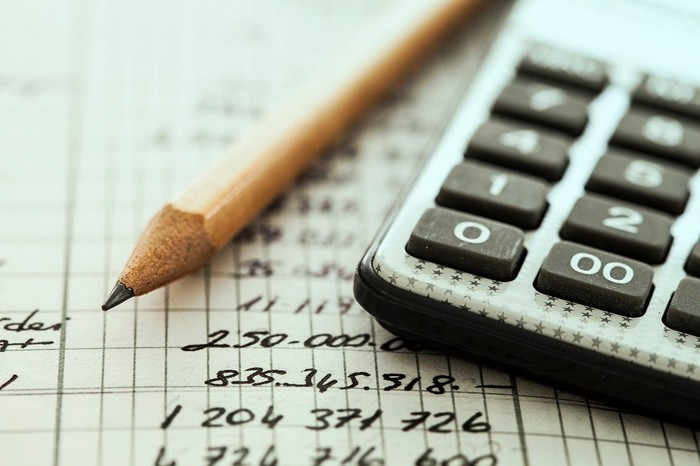 A pencil and calculator sitting on top of a ledger with numbers written on it.