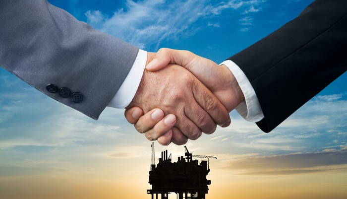 Two men shake hands with an offshore oil rig in the background.