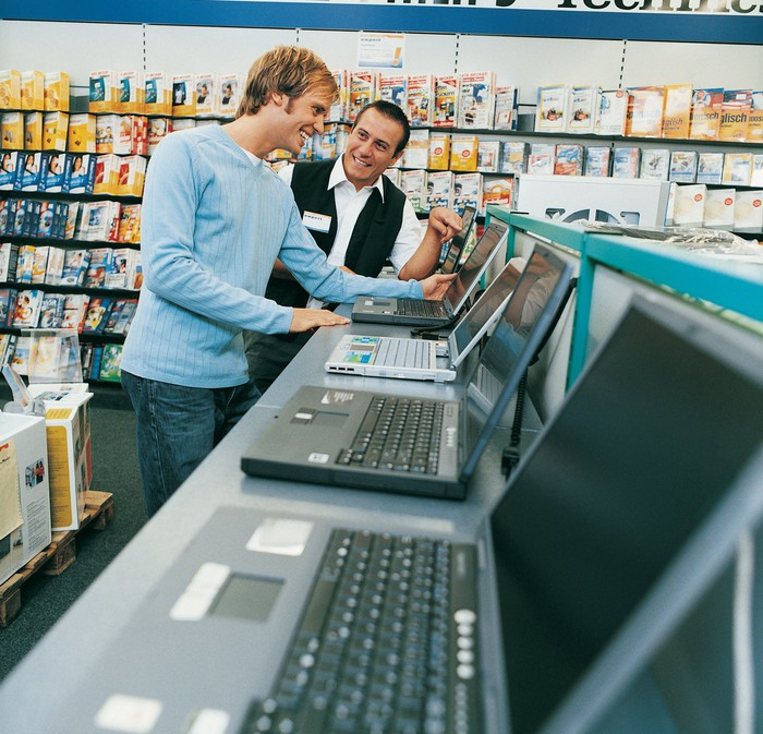 Man looking at a laptop, surrounded by other items to purchase