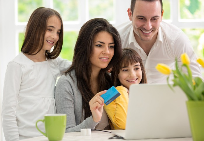 A happy family around a laptop, engaging in e-commerce