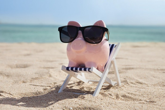 Piggy bank in sunglasses, sitting in a chair on the beach.