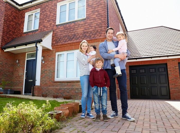 Young family standing in front of a new home.