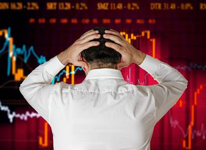 A businessman holds his head with both hands as he stands in front of a red screen showing a declining stock price.