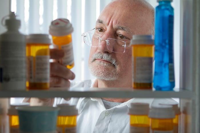 Senior carefully examining bottle of pills.