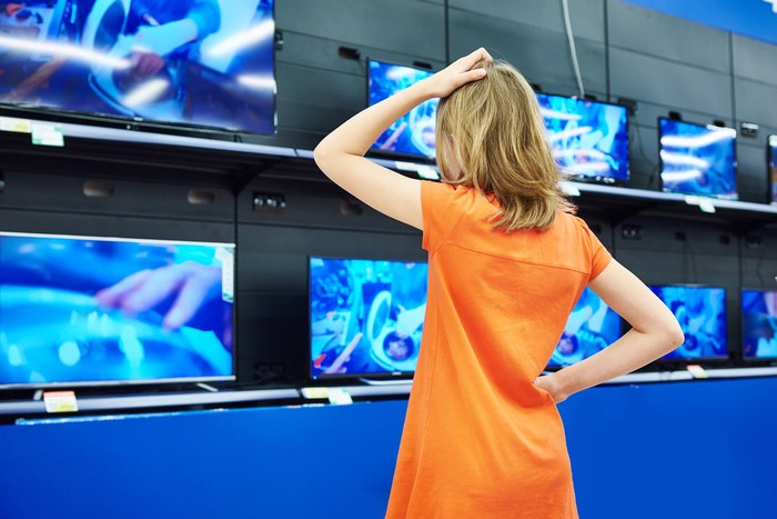 Woman looking at televisions on display.