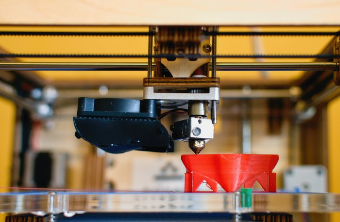 Close-up of a 3D printer printing a red plastic object.