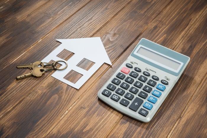 Keys, a calculator, and a cutout of a house lying on a table.
