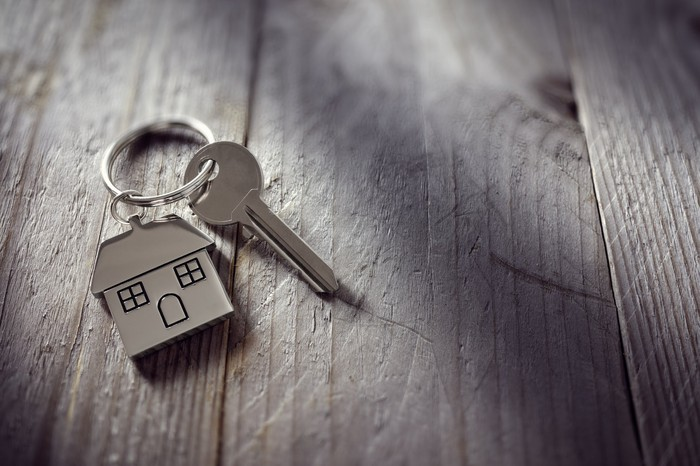 A key on a table, attached to a key ring with a house on it.