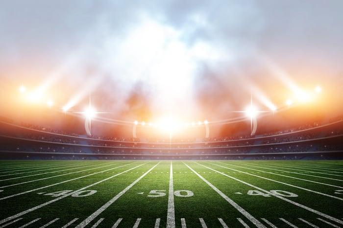 Football stadium at 50-yard line under lights.