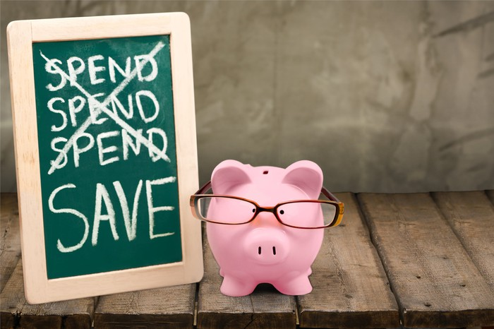 "A piggy bank with glasses, standing next to a chalkboard, with the word ""spend"" crossed out and ""save"" written at the bottom."