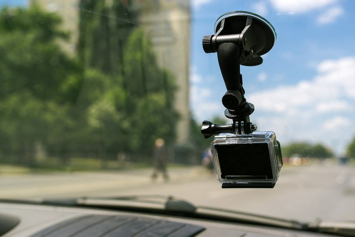 Action camera mounted to a car's front window.